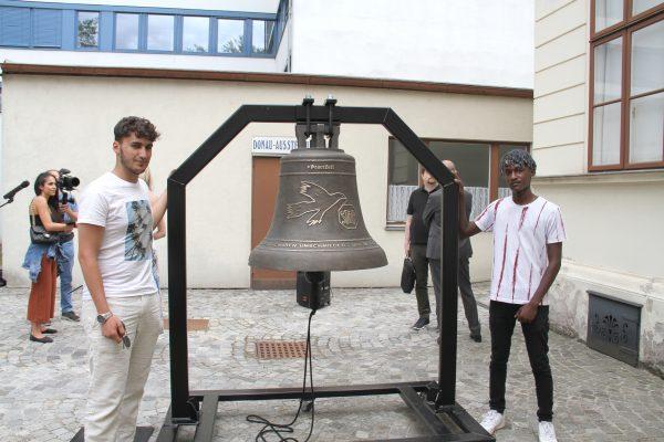 Ucar Abdulvedut und Gibra Mwasi mit der Friedensglocke und dem Gestell, in dem sie aufgehängt ist