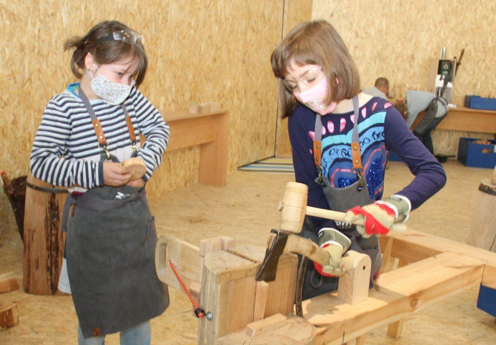 Kinder hacken mit - gesicherter Hacke - und Hammer ein Stück Holz ab