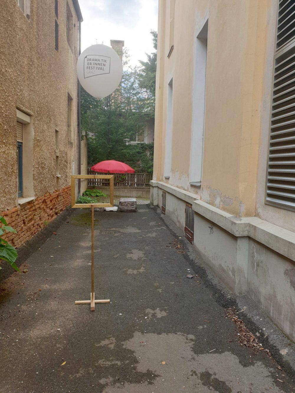Roter Sonnen-/Regen-Schirm in einem schmalen, fast tristen Hinterhof