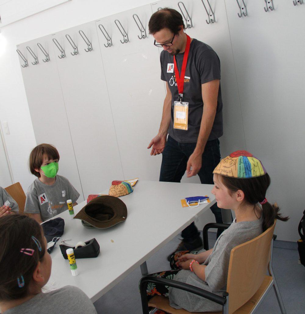 Kinder setzen papierenes, buntes Hirn auf