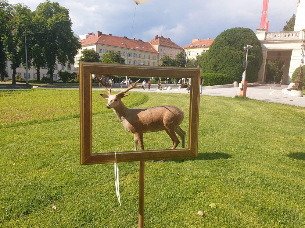 Großer Kunststoff-Hirsch zwischen Grazer Oper und Next Liberty betrachtet durch einen leeren Bilderrahmen