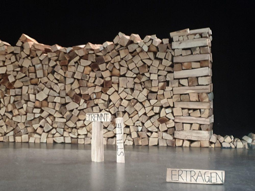 Holzscheite mit Schriftzügen vor einem großen Holzstoß