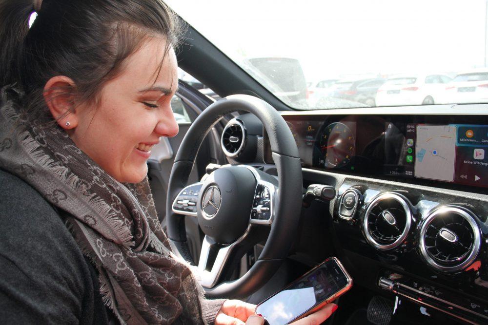Junge Frau bedient Bord-Computer im Auto