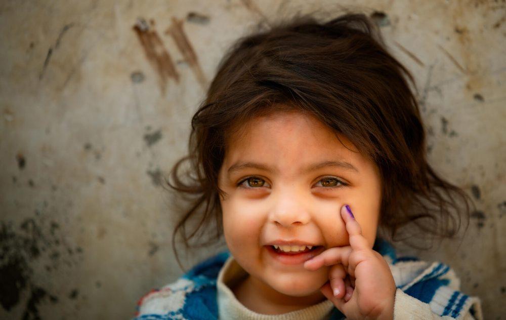 Dreijähriges Mädchen posiert lächelnd für UNICEF-Delegation und zeigt ihren markierten Finger nachdem sie eine Polio-Impfung in Lahore (Pakistan) bekommen hat