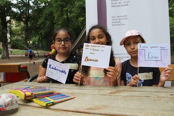 Einige Kinder zeigen ihre selbst gemalten Kinderrechte-Fahnen