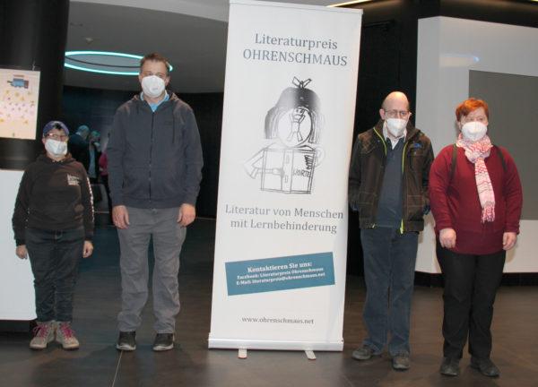 """Vier Literat:innen: Sylvia Hochmüller, Michael Wilhelm (links vom Plakat """"Ohrenschmaus"""") sowie Herbert Schinko und Inge Weinberger (rechts)"""
