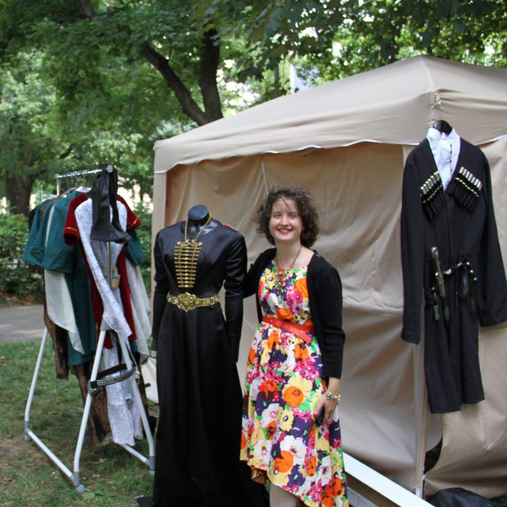Frau bei einer Kleiderstange mit traditionellen Gewändern