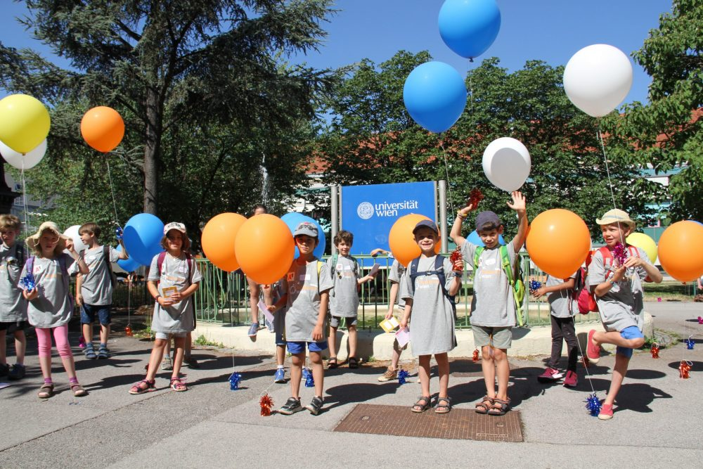 Kiknderuni-Student:innen mit bunten Ballons