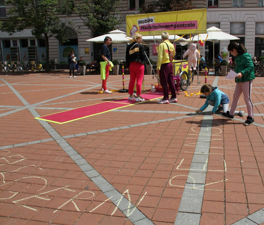 Kinder schreiben mit Straßen-Malkreide systemrelevante Berufe auf den Boden