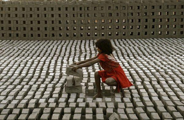 Ganz junges Mädchen schlcihtet Ziegel in einer Fabrik bei Hyderabad (Indien)