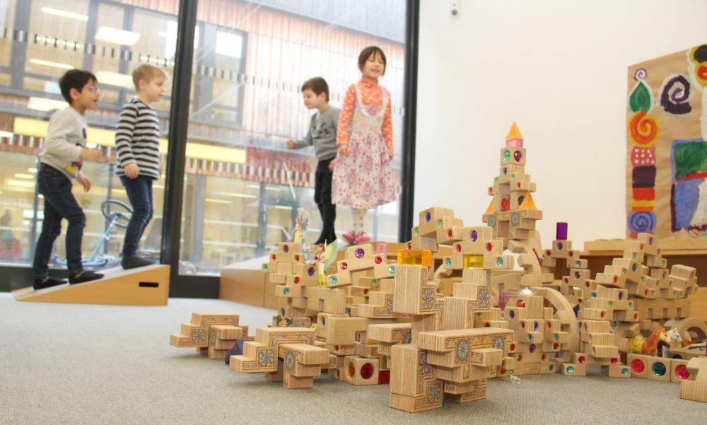 Kinder in einem Kindergarten, gehen über Hindernisse und Bausteine