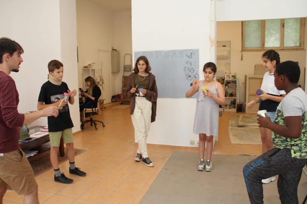 Der Reihe nach spielen Kinder und der Workshopleiter reihum ihre selbst gebauten Instrumente