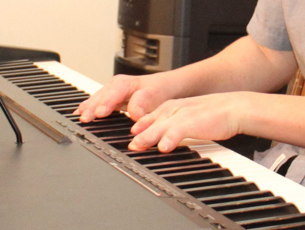 Jugendlicher spielt am Keyboard