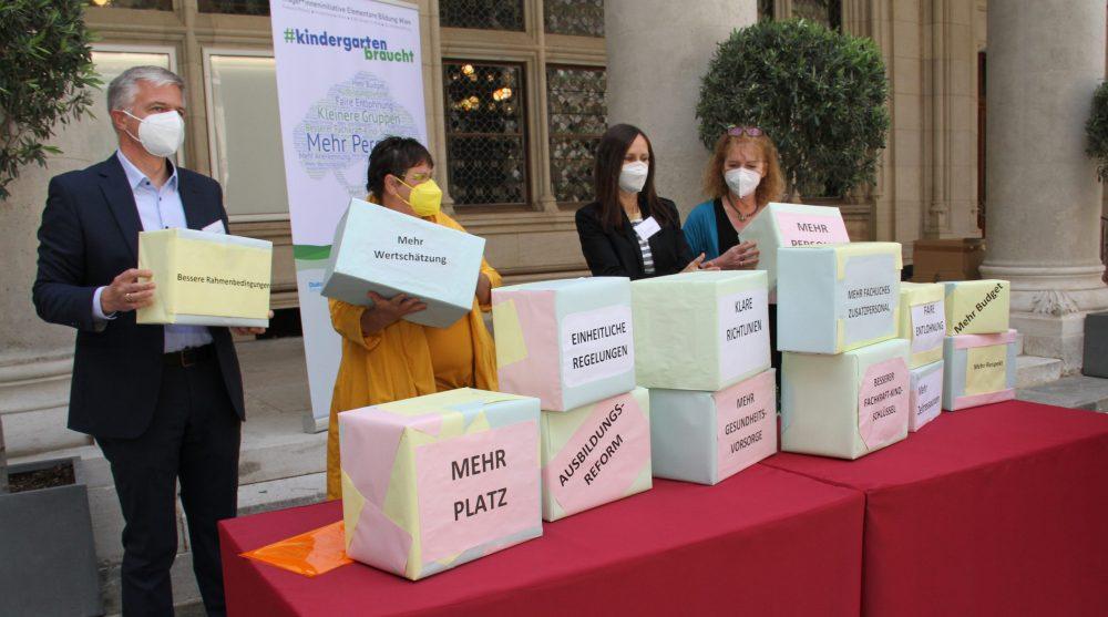 Kleingruppe mit Schachteln auf denen Forderungen stehen