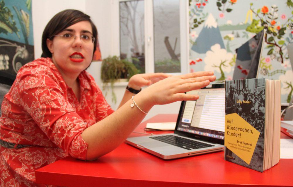 Die Autorin am Laptop, davor das aufgestellte Buch