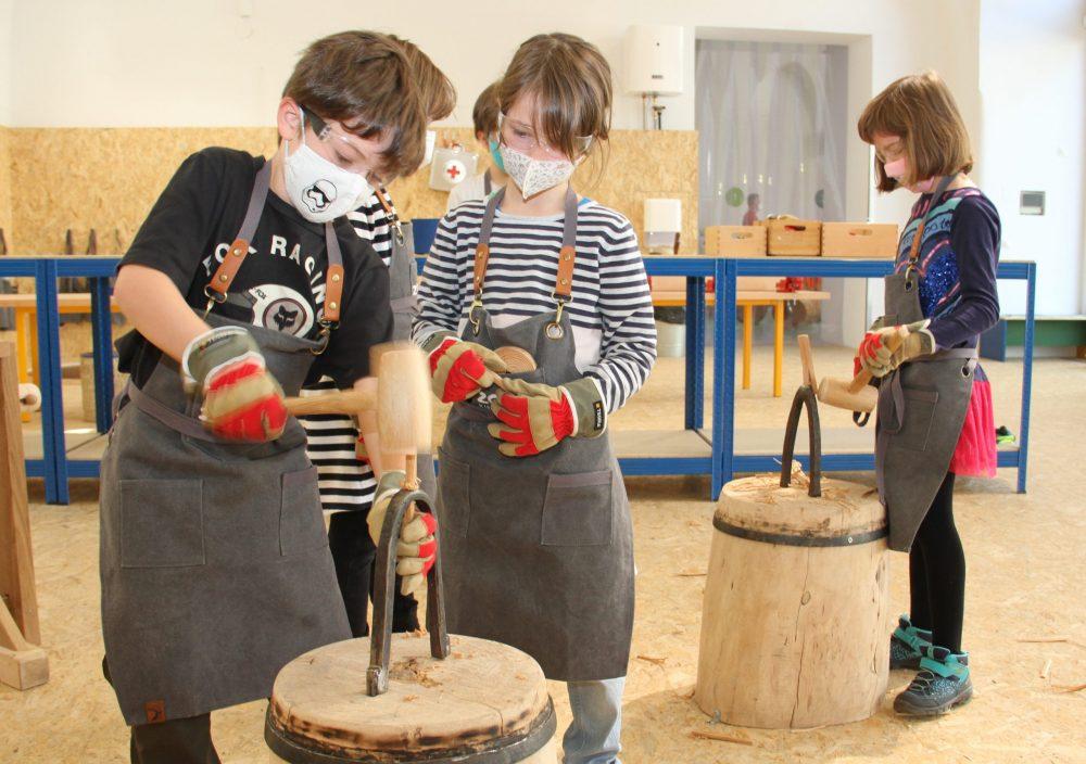 Kind schlägt Holzstück durch Locheisen