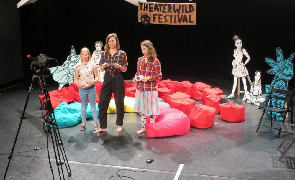 Zwei Kinder und eine Erwachsene stehen vor der Kamera und moderieren