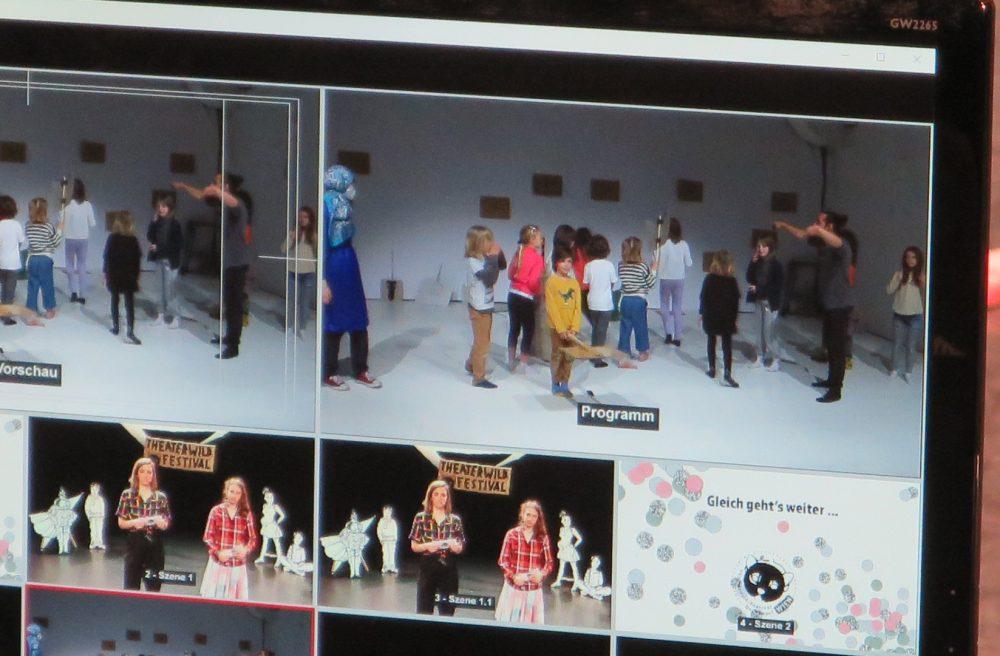 Blick auf einen großen Monitor, auf dem die Aufzeichnung eines Theaterstücks läuft