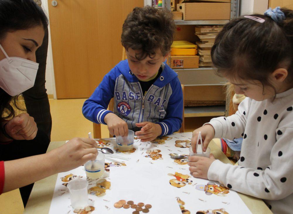 Kinder experimentieren und bringen Kupfermünzen zum Glänzen