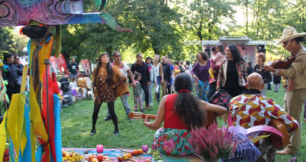 Reihentanz vor kleiner Bühne mit Piñata im Hintergrund