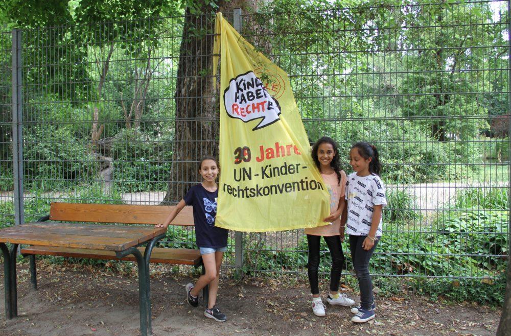 Einige Kinder vor einer großen Kinderrechte-Fahne