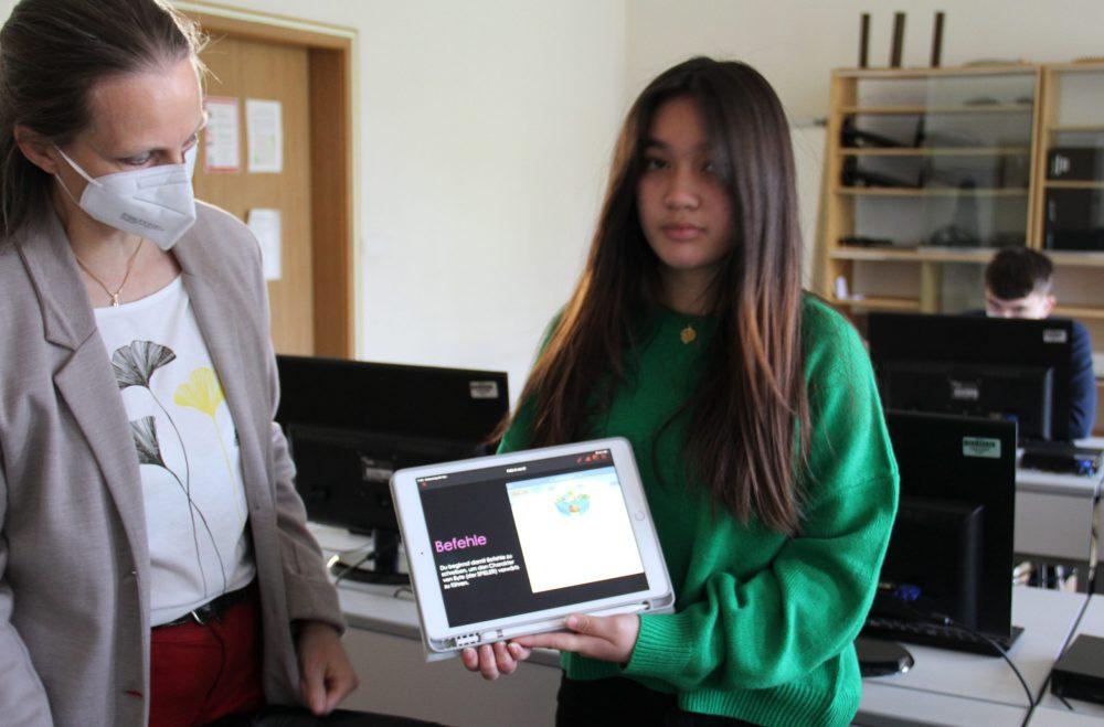 Schülerin Heidi Juare zeigt der Lehrerin Susanne Gruber, wie sie die Spielfigur programmieren kann, damit diese durchs Labyrinth kommt