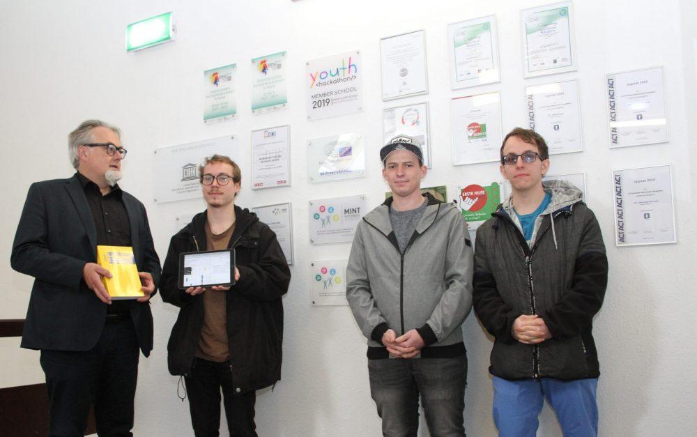 Drei Schüler mit Tablet und Laptop und Direktor mit Buch vor der Schulwand mit Auszeichnungen