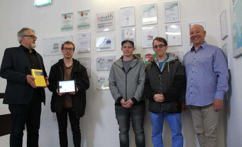 Drei Schüler mit Tablet und Laptop und Direktor mit Buch sowie IT-Lehrer vor der Schulwand mit Auszeichnungen