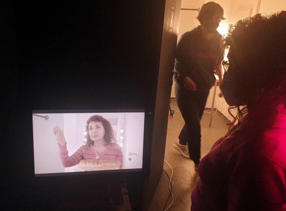 Schauspielerin betrachtet sich selbst im Monitor und die Kamerafrau