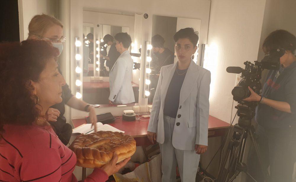 Schauspielerin mit Kuchen, Regisseurin und weitere Schauspielerin, die den Kuchen nicht will