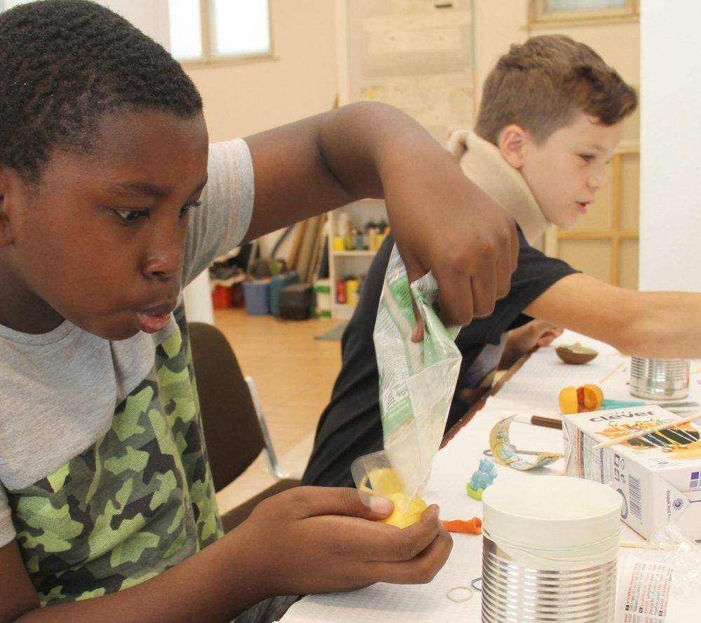 Kinder bauen aus dem Inneren eines Überraschungs-Eies eine kleine Rassel