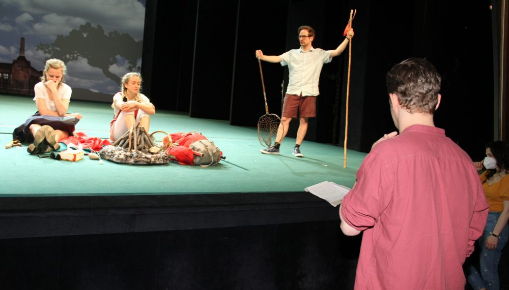 Regie- und Technikleute stehen vor der Bühne, auf der drei Schauspieler:innen eine Lagerfeuer-Szene proben