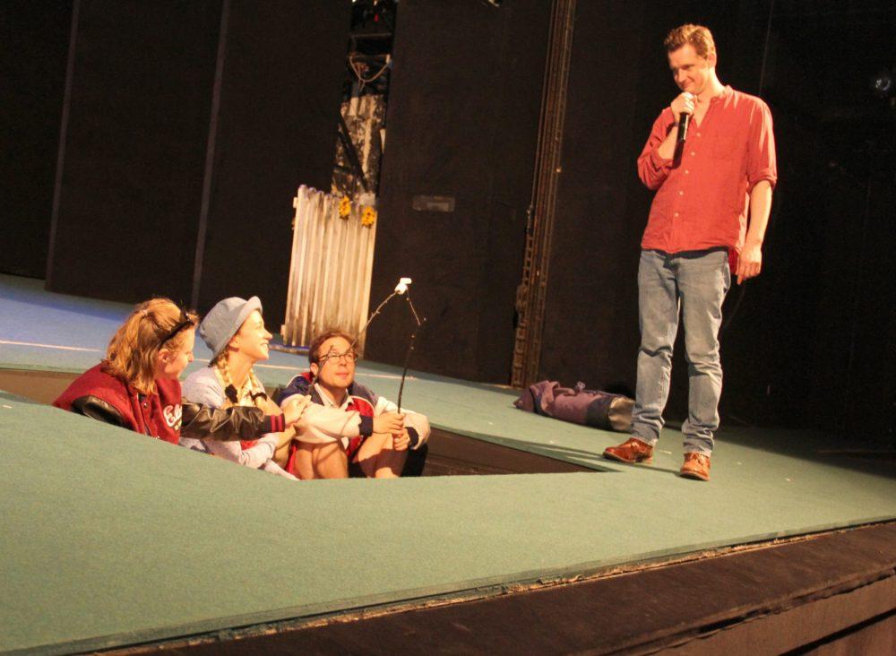 Schauspieler*innen auf der Bühne versinken langsam, Regisseur steht neben dem versenkbaren Teil