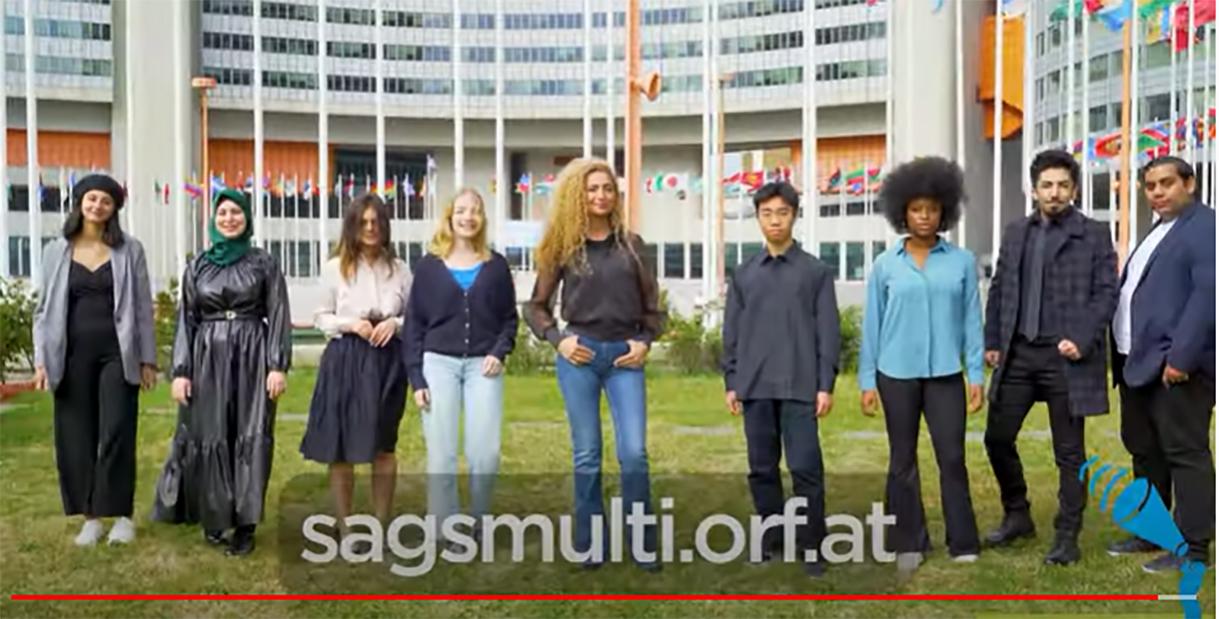Screenshot aus dem Bewerbs-Bewerbungsvideo: moderatorin und einige Jugendliche vor dem UNO-Gebäude in Wien