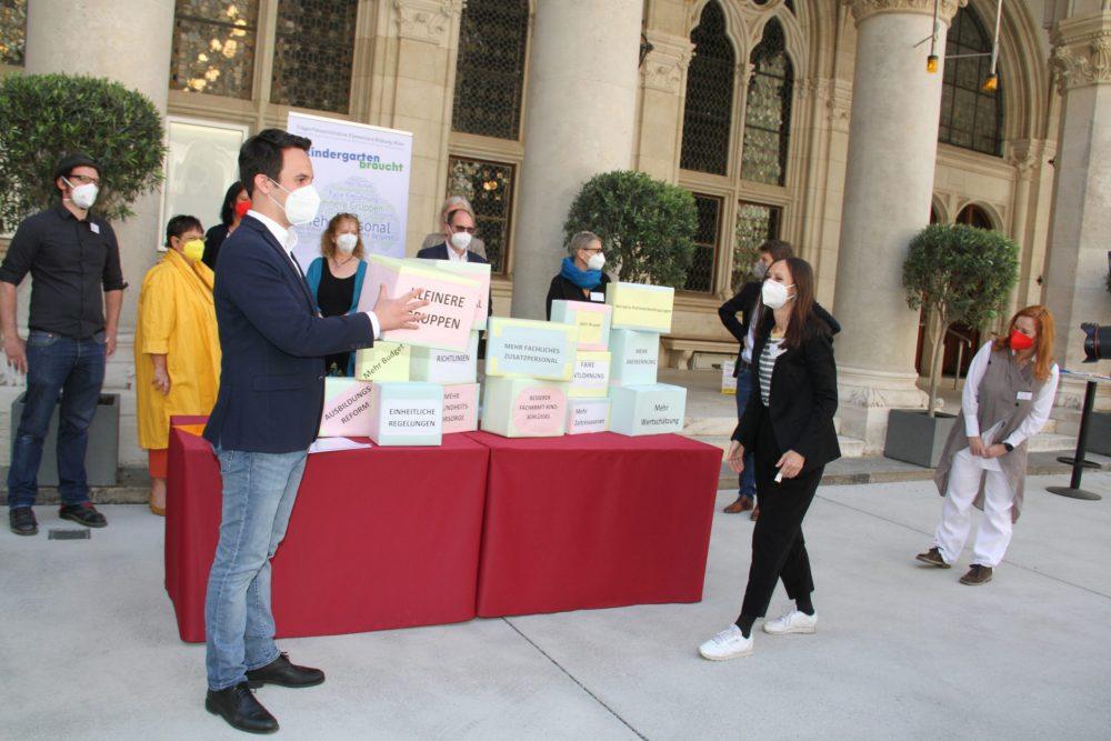 Menschen schupfen Schachteln mit Forderungen zum Kindergarten