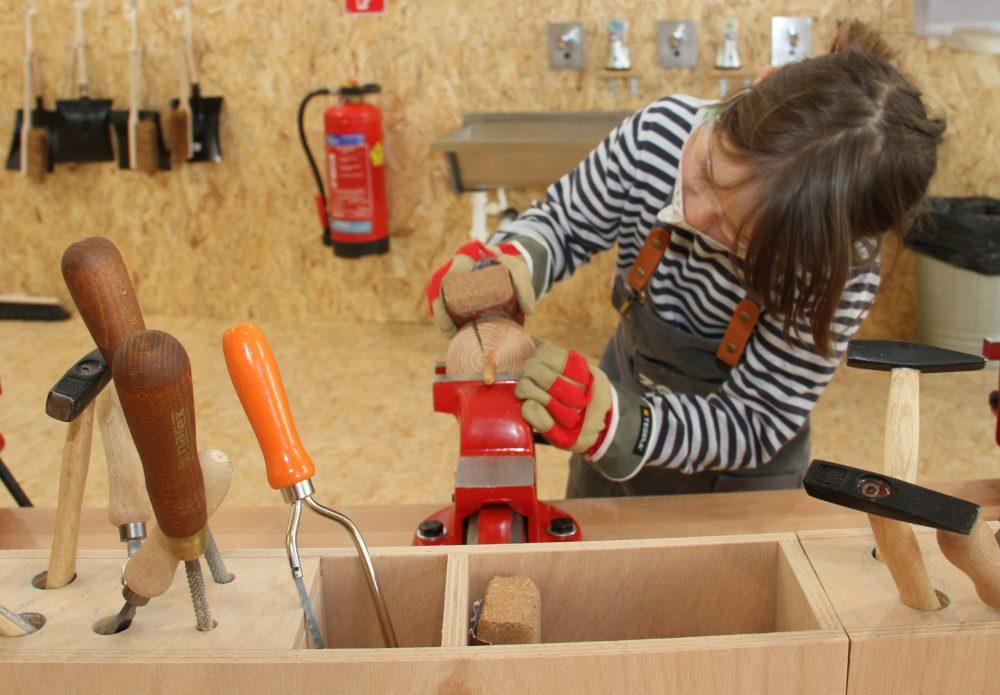 Kinder schleifen die Holzscheiben ab