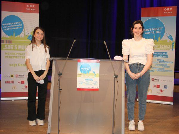 Zwei junge Rednerinnen links und rechts neben dem Redepult auf der bühne des RadioKulturHauses