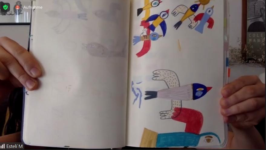 Illustratorin hält Buchseite in die Kamera