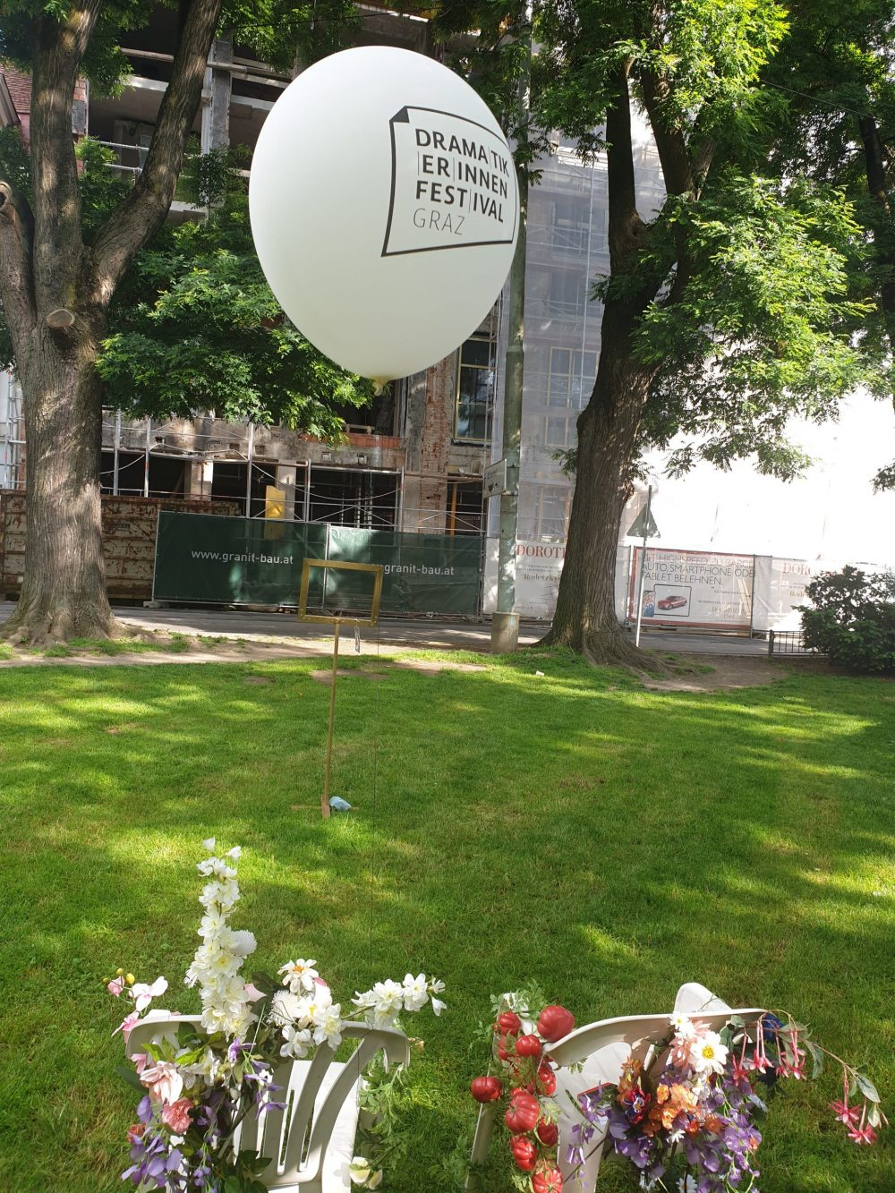 Plastikstühle mit Plastikblumen, ein leerer Bilderrahmen und ein großer weißer Ballon