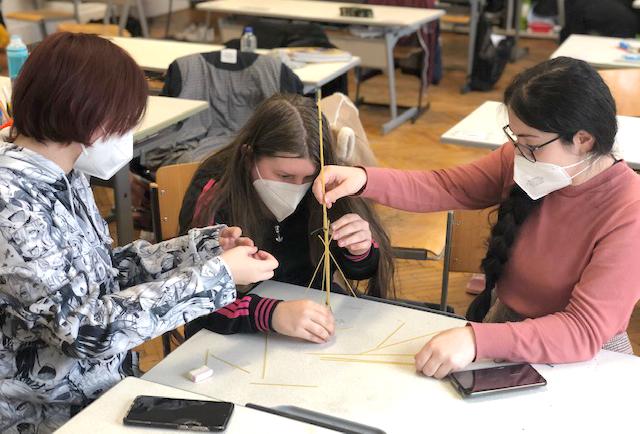 Jugendliche bauen dne ersten Stock eines Spaghetti-Turms