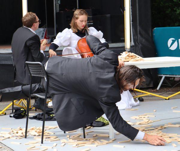 """Szenenfoto aus """"Bis einer heult"""", zwei Männer spielen mit Bausteinen, eine Frau am Cello"""