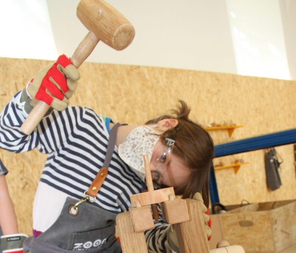 Kind schlägt Holzspitz durch Loch der Holzscheibe