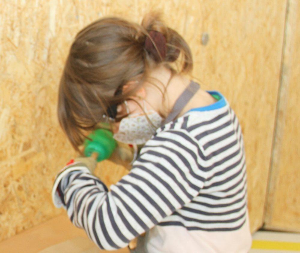 Kinder spitzen mit einem Spitzer den Holzstab
