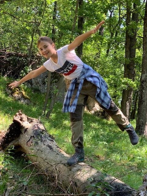 Mädchen balanciert auf einem liegenden Baumstamm