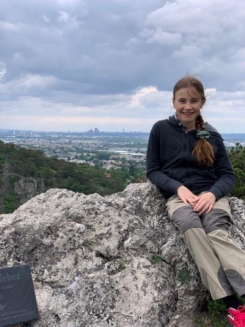 Mädchen sitzt auf einem Felsen im Gebirge