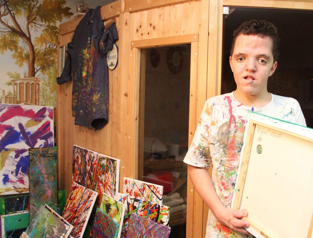 Jugendlicher mit Signierstempel für seine Bilder