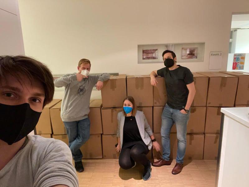 Mitarbeiter*innen mit schon gefüllten, verpackten Kartons
