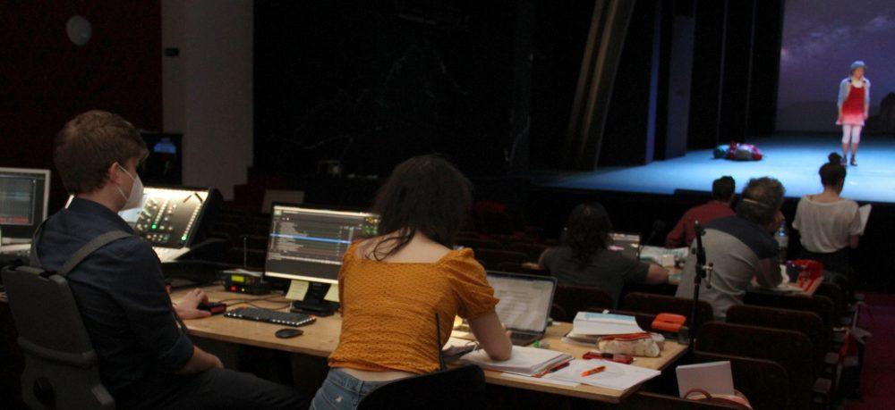 Langes Brett über eine Publikumssitzreihe mit Computern. Von hier aus wird die Tontechnik gesteuert