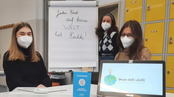 Drei jugendliche Schülerinnen mit Laptop und Plakaten