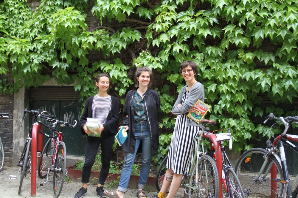 Drei junge Frauen mit Büchern stehen im WuK-Hof vor einer begrünten Wand und zwischen Fahrrädern: Kathi Pech, Sara Schausberger und Greta Egle